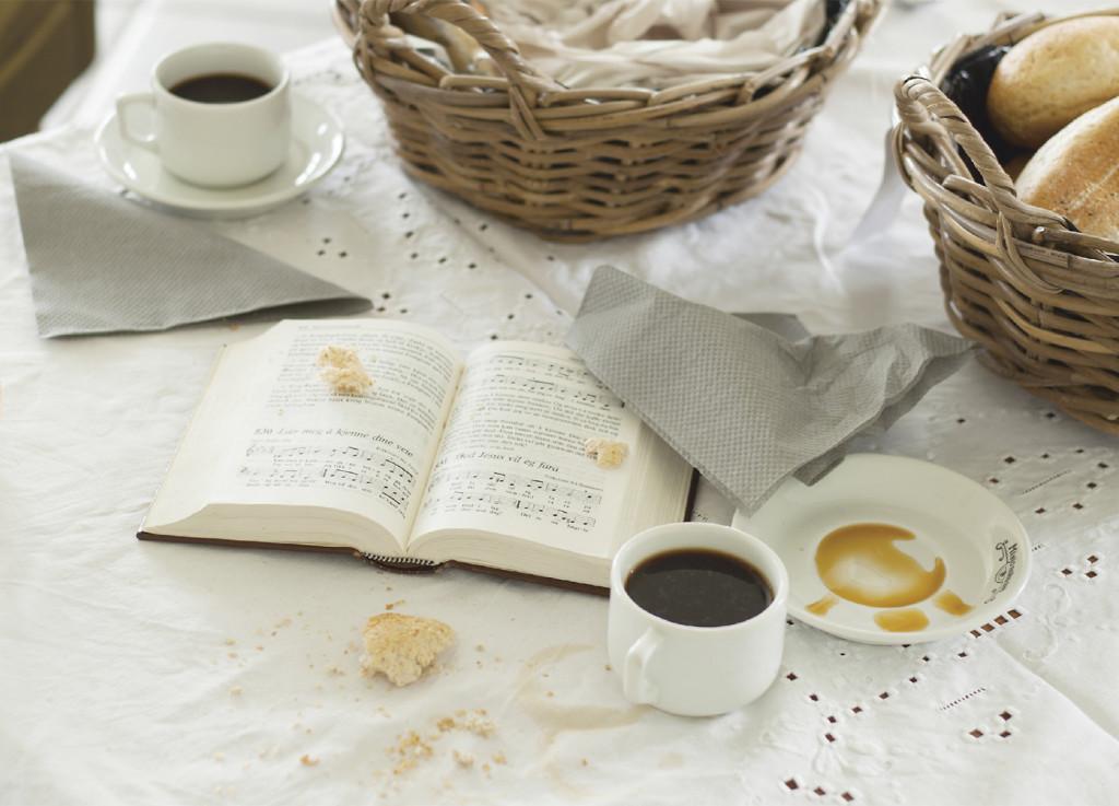 Bildet viser et bord med kaffekopper, servietter, en sangbok og brød.